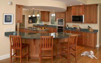 curved kitchen island with marble countertop plus wooden chairs and wooden floor and pendant lighting