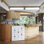curved kitchen island with wooden countertop plus stylish lighting and wooden floor and glass windows with curtains