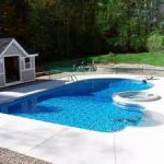 cute heart saped swimming pool with large deck and surrounded with greenery aside lovely small house in white tone