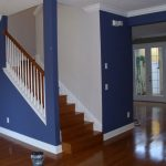 dark blue interior exterior painting with wooden laminating floors and stairs plus glass doors and windows
