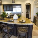 dark curved kitchen island with stool chairs and marble countertops plus sink and plant pot and kitchen cabinets plus tile floor