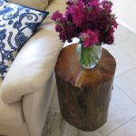 dark stained side table made from tree stump a beautiful flowers in glass vase a white sofa with blue patterns white ceramic flooring