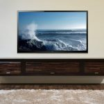 dark stained wood floating TV console in rustic style a grey white fury rug for floor darker wood planks flooring a very large flat TV  a frameless photograph