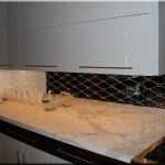 diagonal mirror backsplash for modern kitchen white marble countertop some ornamental items a gas stove minimalist top cabinet system black bottom drawers and white bottom storages with metal handle
