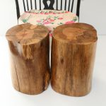 double tree stumps side table in natural wooden tone upon white tiles flooring design aside floral patterned fabric on chair