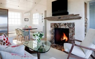 driftwood mantle fireplace as media stand a traditional fireplace with natural stones frame a rocking chair in white a comfy sofa with beautiful pattern pillows glass top table a TV set