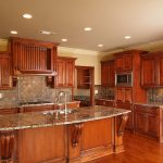 elegant kitchen remodeling from wood material with marble countertops plus island with sink together with tile backsplashes and microwave plus laminating wood floor