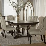 exclusive white tufted cowhide dining chair with white orchid on the wooden table with arch entrance above a patterned rectangle modern area rug on the floor