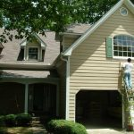 exterior painting with beige color schemes plus grey roof and garage plus glass windows with shutters