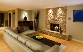 fancinating waterproofing basement floor with wooden laminating floor for living room with leather sectional sofa and wooden coffee table plus hard stone wall plus fireplace