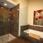 fancy master bathroom remodel with bathtub and dark tile floor and wall combined with picture and walk in shower glass wall