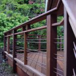 firm and strong horizontal deck railing design with metal combination with wooden deck flooring aside lush vegetation