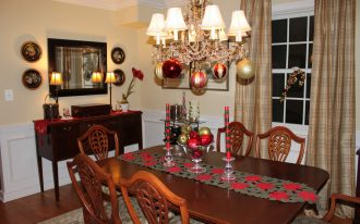 flashing bright classic chandelier with christmas ball above simple floral red centerpiece on wooden rectangle table and wooden chairs and vanity beneath black framed mirror