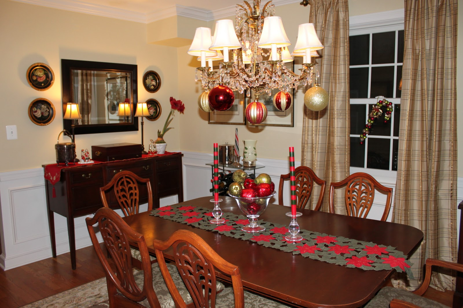flashing bright classic chandelier with christmas ball above simple floral red centerpiece on wooden rectangle table