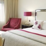 flashing mirrored white headboard with floral patterned white pillows and white pink quilt and black table with pink table lamp aside pink armchair