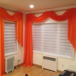 flashing orange horizontal window blind design with white additional drape on white window upon crea floor
