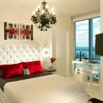 flashing red pillows design above brown quilt on white bedding set above cow patterned rug beneath funky chandelier and picture gallery above tufted headboard