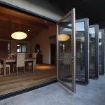 Folded La Cantina Doors As The Front Door A Series Of Rattan Dining Furniture A Simple But Elegant Pendant Lighting Fixture Wood Floors