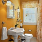 fresh small bath remodel with yellow paint and floral shower curtain plus toilet and wash basin with mirror and wall scones plus window