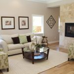 gas firplace as the separator of two rooms a set of cozy living room furniture white carpet two decorative frames wood floor idea