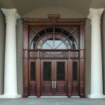 gorgeous big wooden arch door design between two concrete pillars with black glass accent and pella storm door