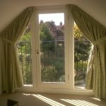 gorgeous coned half curtain rod design with green curtain covering glass door in loft with cream floor