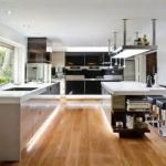 gorgeous galley kitchen remodel with laminated wooden flooring style beneath white cabinetry with maximal lighting and black storage with posh island
