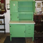 gorgeous green antique kitchen cabinet design with open and close storage with four legs and drawers and large slot and white countertop aside vintage wall mirror above brown flooring style
