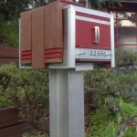 gorgeous modern marroon mail box design with brow wooden cover and stainless steel accent with concrete beam in the middle of greenery
