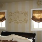gorgeous small window design with  brown rolled drape ides in bedroom with black bedding and white pillows and wallpaper