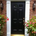 gorgeous white door casing style of black wooden door with modern molding patten between reddish brick wall and potted plants