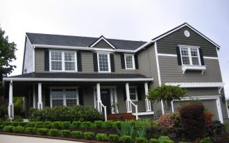 great houses with black shutters and gray wall plus white windows and black front door plus garden and wood garage door