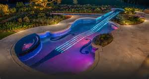 guitar shaped swimming pool desin with unique patio flashed with modern lighting idea aside lush vegetation