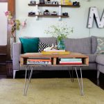 hairpin coffee table with under shelves for books light gray sofas with decorative pillows floating wood shelves for decorative items gold-tone fury carpet for living room