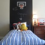 high chalkboard headboard with decorative picture  stripe patterns bedcover two animal stuffs wood side-table with draw and cabinets