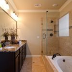 impressive master bathroom remodel with bathtub and stylish bathroom vanity units with dark wooden and sink plus large mirror and walk in shower with glass wall and vase