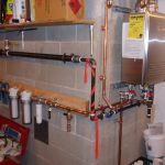 indoor tankless water heater installation on brick walls with metal pipes and woods