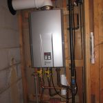 indoor tankless water heater installation with plumbing and metal pipes and woods on wall
