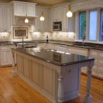 kitchen remodeling northern va with light wood cabinets and kitchen island with sink and marble countertop plus pendant lighting and laminating floor