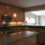 kitchen remodeling northern virginia with wooden cabinets and coountertop plus steel kitchen appliances and sink and beautiful pendant lighting