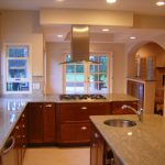 kitchen remodelling contractors with wooden cabinetry and marble countertops plus sink and windows plus LED lighting