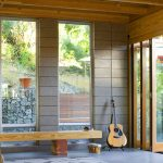 La Cantina Folding Glass Door For Modern Front Door A Long Wood Bench A Comfy Chair Large Glass Windows An Outdoor Reclining Chair