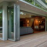 La Cantina Glass Door With Clear Lines In A Contemporary Home Living Wood Planks Floors For Outdoor A Set Of Wood Outdoor Furniture A Set Of White Dining Chairs  Grey Sofa For Living Room