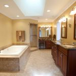 large bathroom remodeling with bath tub and double bathroom vanity unit with sink and marble countertop plus mirror and natural tile floor