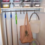 large broom closet design with stainless pole hooks and several plastic storage with bag and vacuum cleaner