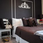 large chalkboard headboard design with white line borders  dark brown bedding with dark brown pillows  small white wood chair animal-skin carpet