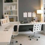 large corner home office desk for two persons with mounted book racks and and cabinets stylish white chairs with wheels simple gold-stand table lamp