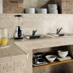 light cream ceramic tiles for countertop and backsplash two  stainless steel sinks and faucets a stainless steel blender a pair of juice glasses and a juice jug a pile of white bowls and plates