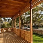 Long Spacious Terrace Design With Wooden Ceiling And Wooden Floor And Wooden Horizontal Deck Railing With White Seating Aside Grassy Meadow Beneath Shady Tree