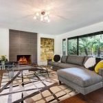 luxurious and spacious living room design with open plan and geometric patterned area rug beneath stunning ceiling lamp upon wooden floor with two sided fireplace
